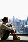 Woman sitting on a window sill while looking at Empire State Building, Rockefeller Center, Manhattan, New York City, New York, USA