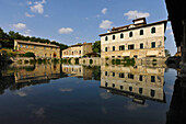 Reflection of houses in a large water basin, Bagno Vignoni, Tuscany, Italy, Europe
