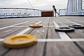 Woman plays shuffleboard aboard cruise ship MS Astor, Transocean Kreuzfahrten, MR, near Kiel, Schleswig-Holstein, Germany