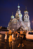 Young Russian women party in front of limousine at Church of the Savior on Spilled Blood (Church of the Resurrection) at night, St. Petersburg, Russia