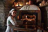 Woman in medieval costume bakes bread rolls and pies at Inn Krug Korts restaurant at Town Hall Square (Raekoja Plats), Tallinn, Harjumaa, Estonia