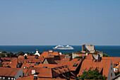 Overhead of Visby rooftops with cruise ship Silver Whisper (Silversea Cruises) anchored in Baltic Sea, Visby, Gotland, Sweden