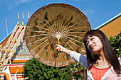 Asian woman with umbrella at Wat Pho, Temple of the Reclining Buddha, Bangkok, Thailand