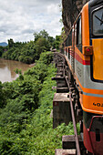 Modern locomotive of tourist train on wooden trestle viaduct of Trans River Kwai Death Railway at Saphan Tham Krasae, near Kanchanaburi, Thailand