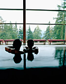 Couple in indoor pool looking out of a panorama window, Vigiljoch, Lana, Trentino-Alto Adige, South Tyrol, Italy