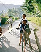 Kids riding their bikes to school, Anse La Reunion, La Digue, La Digue and Inner Islands, Republic of Seychelles, Indian Ocean