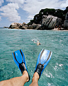Snorkelling in shallow water over coral reef near tiny Coco Island, La Digue and Inner Islands, Republic of Seychelles, Indian Ocean