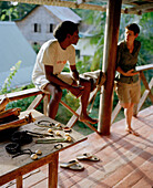 Field guide and jewellery maker Silvin Fanchette and author on the terrasse of his typical old island style house in La Passe, La Digue and Inner Islands, Republic of Seychelles, Indian Ocean