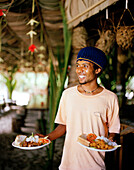 Waiter at restaurant Loutier Coco on Grand Anse beach, south eastern La Digue, La Digue and Inner Islands, Republic of Seychelles, Indian Ocean