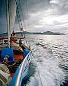Transport sailer La Belle Praslinoise on its way to La Digue, dark rain clouds over La Digue, La Digue, La Digue and Inner Islands, Republic of Seychelles, Indian Ocean