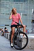Woman cycling on an e-bike, bike tour, Schlossplatz, Museum of Arts, Stuttgart, Baden-Wurttemberg, Germany