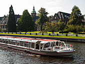Alster steamer on the Alster river in front of Saint Johannis Abbey, Hanseatic City of Hamburg, Germany