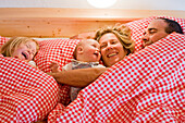 Family lying in bed laughing