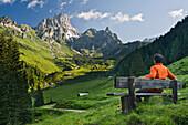Young man on a bench looking at the view, Hofalm, Bischofsmuetze, Salzkammergut, Salzburg, Austria, Europe
