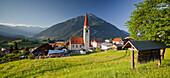 Mountain village with church, Tschirgant mountain in the background, Tyrol, Austria