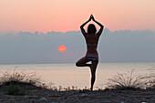 Woman practising Yoga at sunrise, Mediterranean Sea, Lykia, Turkey, Europe