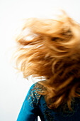 Young woman with blond hair, view from the back, blurred motion, close up (studio)