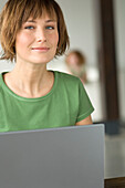 Young woman using laptop computer, looking at the camera