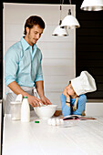 Mid adult man making a cake and his son in the kitchen