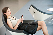 Woman reclining in a chair and text messaging with a mobile phone