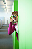 Businesswoman looking through binoculars in an office corridor