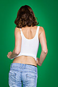 Young woman in tank top and jeans, rear view