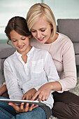 Woman assisting her daughter in using a digital tablet