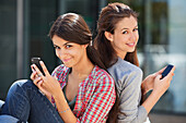 Portrait of two young women sitting back to back and using mobile phones