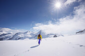 Mountaineer crossing a snowfield above Concordia, Grindelwald, Bernese Oberland, Switzerland