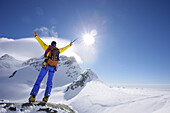 Mountaineer at the summit of Jungfraujoch, Jungfrau in the background, Grindelwald, Bernese Oberland, Switzerland