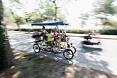 Family in a four person carriage cycle, Lido di Venezia, Venice, Veneto, Italy