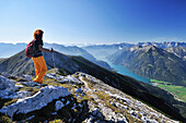Woman walking at Unnutz with view to lake Achensee, Rofan range and Alpine main ridge, Unnutz, Unnuetz, Rofan, Tyrol, Austria