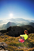 Woman sitting at the summit and looking towards the Inn valley and the Kaiser mountain range, Brunnstein, Bavarian Prealps, Upper Bavaria, Bavaria, Germany