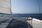 Woman relaxes on net of catamaran SY Azzura, Ocean Blue Oman cruises, during sailing excursion, Muscat, Masqat, Oman, Arabian Peninsula