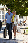 Young couple, promenading with shopping bags, Schlossplatz, New Castle, Stuttgart, Baden Wurttemberg, Germany