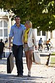 Young couple, promenading with shopping bags, Schlossplatz, New Castle, Stuttgart, Baden Wurttemberg, Germany