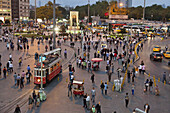 People and tram at Taksin square in the evening, Cumhuriyet Abidesi monument, Istanbul, Turkey, Europe