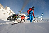 Helicopter and skiers in the mountains, South Tyrol, Italy, Europe