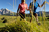 Two hikers with hiking poles in an alpine meadow, South Tyrol, Italy, Europe