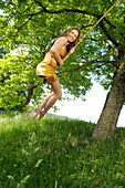 One woman on a swing wearing summer dress, South Tyrol, Trentino-Alto Adige, Italy