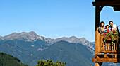 Family on a balcony in front of mountain range in the sunlight, Luesen, Alto Adige, South Tyrol, Italy, Europe