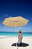 Woman under umbrella on beach, Anguilla