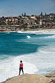 Woman standing on rock over looking Mackensies and Tamarama Bay, near Bondi Beach, Sydney, New South Wales, Australia