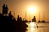 People watching the sunset on rocks beside Benirras beach, Ibiza, Spain.