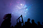 Silhouettes of people watching firework display, Newick, England