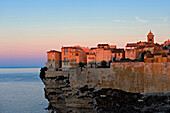 The first rays of sunlight hitting the medieval fortified town of Bonifacio, Bonifacio. Corsica. France.