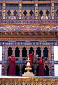 Monks cleaning windows at monastery, Punakha, Bhutan