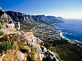 Hiker looking at Camps bay, sitting on top of hill, side view, Capetown, South Africa