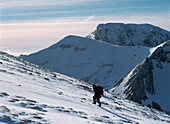 Woman going up snowy slope near the top of Aonach Mor with Ben Nevis behind, Inverness-shire, Scotland