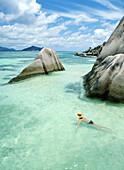Woman swimming close to shore beside boulders, Anse Source D'Argent, La Digue, The Seychelles